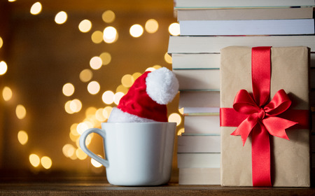 white cup with Christmas hat and books on Fairy lights background