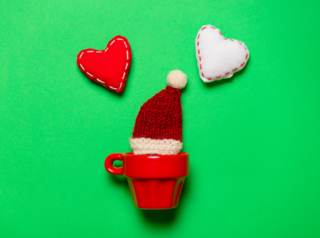 Red cup and Christmas hat and heart shapes on green background