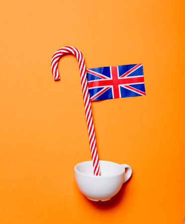 White cup and candy cane with United Kingdom flag on orange background Stock Photo