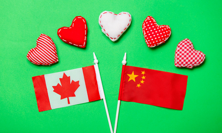 Valentines Day heart shapes and flags of Canda and China on green background 스톡 콘텐츠