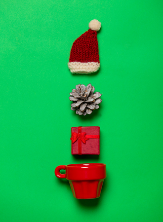 Red cup and Christmas gifts on green background