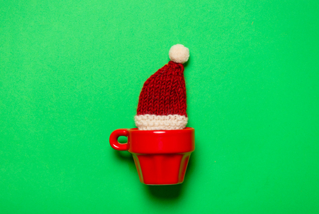 Red cup with Santa Claus hat in it on green background.