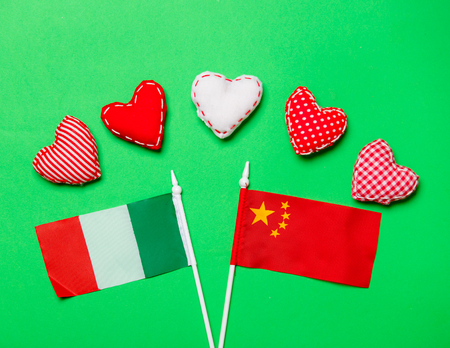 Valentines Day heart shapes and flags of Italy and China on green background Stock Photo