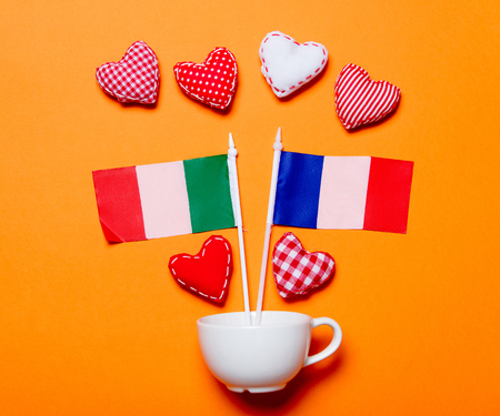 White cup and heart shapes with France nad Italy flags on orange background