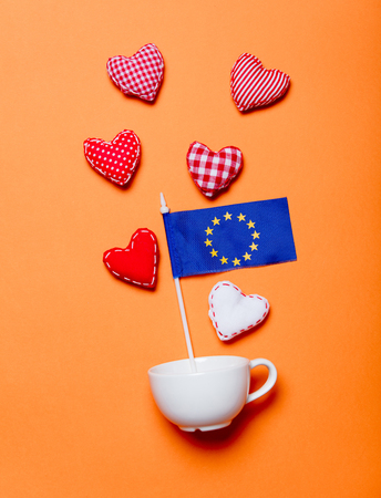 White cup and heart shapes with Europe Union flag on orange background Stock Photo