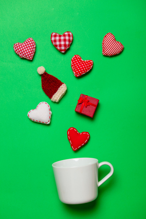 White cup and Christmas gifts and heart shapes on green background Stock Photo