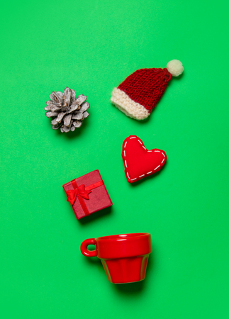 Red cup and Christmas gifts and heart shape on green background