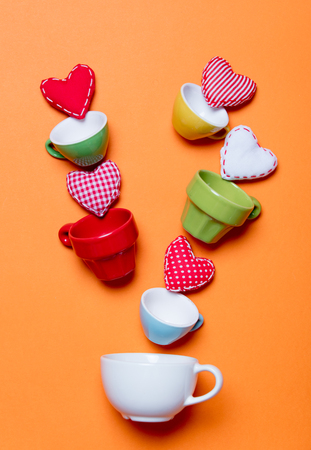 Heart shapes and color cups on orange background. Above point of view  Stock Photo