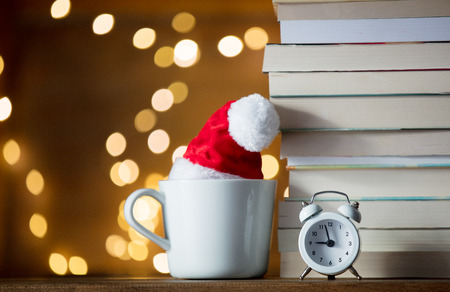 Vintage alarm clock and pile of books with cup and fairy lights on wooden background Stock Photo