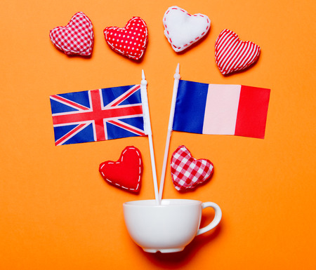 White cup and heart shapes with France and United Kingdom flags on orange background