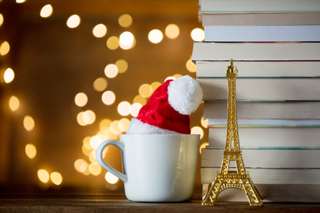 white cup with Christmas hat and Eiffel tower and books or Fairy lights background