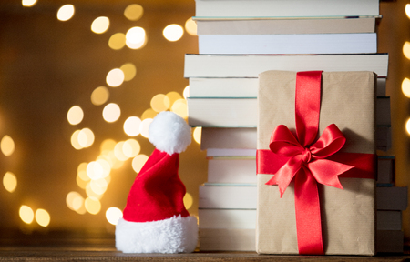 Christmas gift box, Santa Claus hat and pile of books with fairy lights on background
