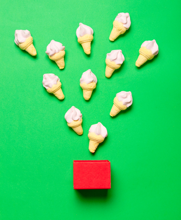 marshmallows with red box on green background Stock Photo