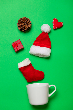 White cup and Christmas gifts and heart shape on green background Stock Photo