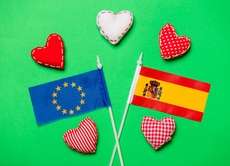 Valentines Day heart shapes and flags of Spain and Europe Union on green background