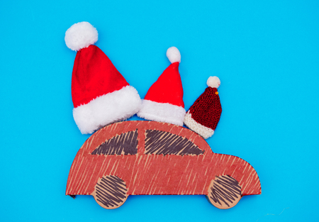 Red handmade car delivery with Christmas hats on blue background
