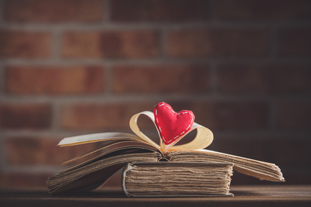 Heart shape and old book on wooden table at brick wall background. Library