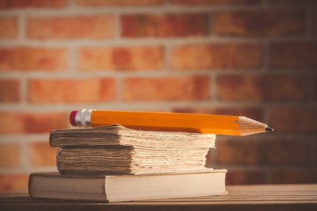 big pencil and old books on wooden table at brick wall. Library Stock Photo