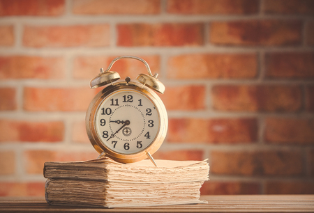 vintage alarm clock and old books on wooden table at brick wall background. Library Foto de archivo