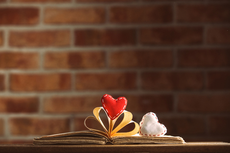 Heart shapes and old book on wooden table at brick wall background. Library Stock Photo