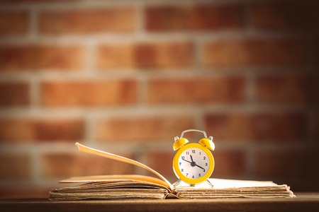 vintage alarm clock and old books on wooden table at brick wall background. Library Stock Photo