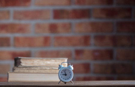 vintage alarm clock and old books on wooden table at brick wall background. Library Archivio Fotografico