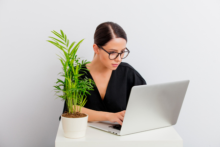 Pretty redhead caucasian woman in black dress and computer with palm sitting at white table in lagom style on white background