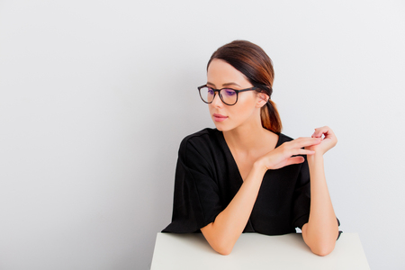 Pretty redhead caucasian woman in black dress and eyeglasses sitting at white table in lagom style on white background