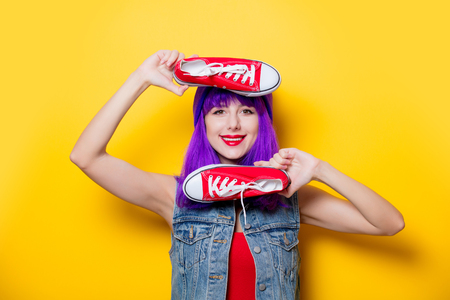 Portrait of young style hipster girl with purple hair and red gumshoes on yellow background