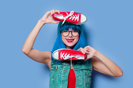 Portrait of young style hipster girl with blue hair and red gumshoes on blue background