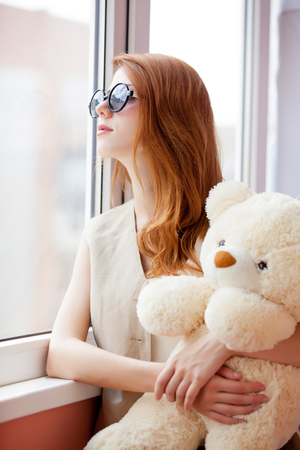 Redhead girl in sunglasses with teddybead toy missing near window