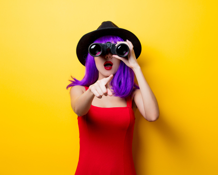 Portrait of young style hipster girl with purple hairstyle and binoculars on yellow background Фото со стока