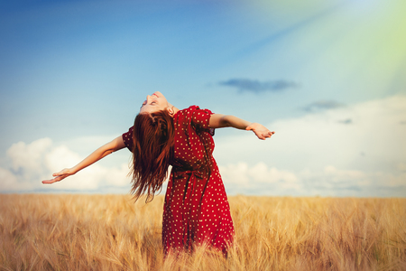 Young redhead girl with open hands standing at wheat field in summer time
