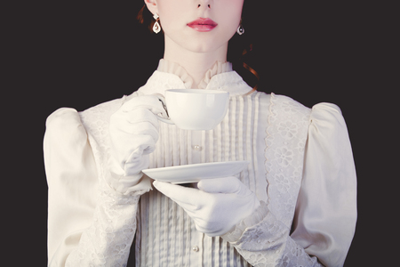 Young redhead woman in white victorian era clothes with cup of tea on black background. Stock Photo