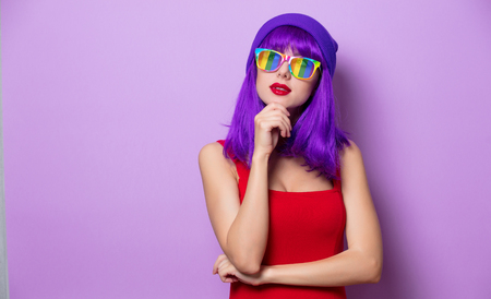 Portrait of young style hipster girl with purple hair and rainbow eyeglasses on pink background