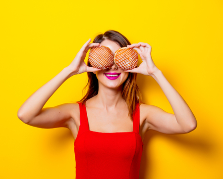 Young girl in red dress with donuts on yellow background Stock Photo