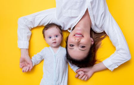 Mother and little child lying down on yellow background