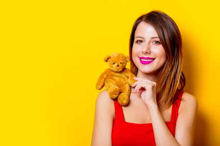 Young girl in red dress with teddy bear toy on her shoulder yellow background Stock Photo