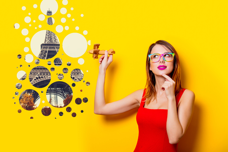 Young girl in red dress with airplane toy dreaming about travel to Paris on yellow background Stock Photo