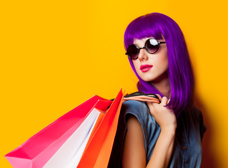 Young girl with purple hair and shopping bags on yellow background