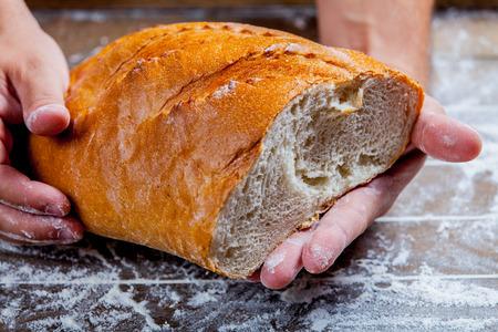 gluten free baked bread in baker hands on wooden background