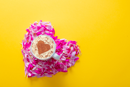 Pink and purple flower petals in heart shape and cup of cappiccino on yellow background.