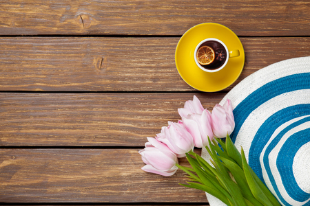 Cup of english tea with spring tulips and hat on wooden background