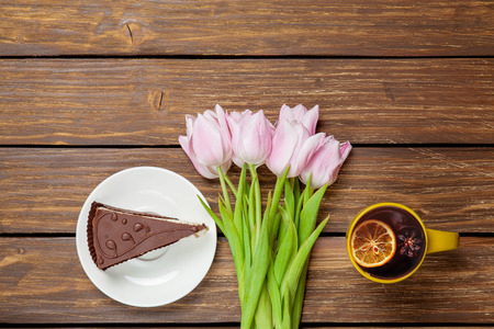 Cup of english tea with spring tulips and cake on wooden background