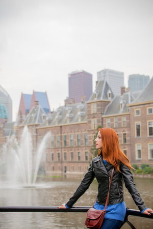 Young girl in sunglasses standing near fountain in Hague, Netherlands