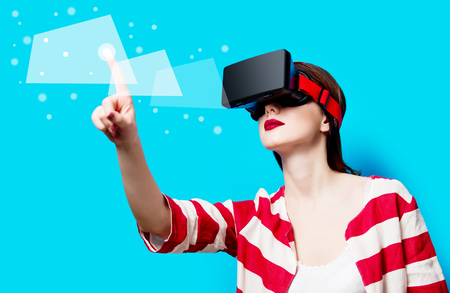 portrait of beautiful young woman with virtual reality gadget on the blue background