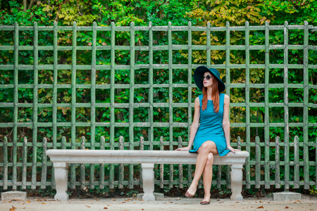 Young redhead girl in sunglasses in Versailles park in summertime.