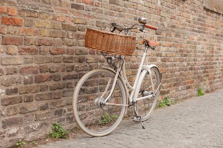White bike with basket standing near brick wall in Brugge, Belgium  Stock Photo