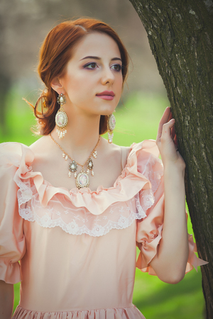 Young redhead girl in Victorian era clothes standing near tree in the park Stockfoto