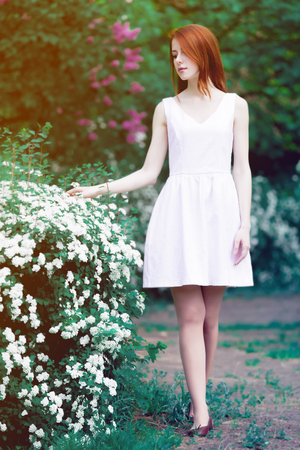 Young redhead girl in white dress standing near a tree and bushes in the park. Springtime season